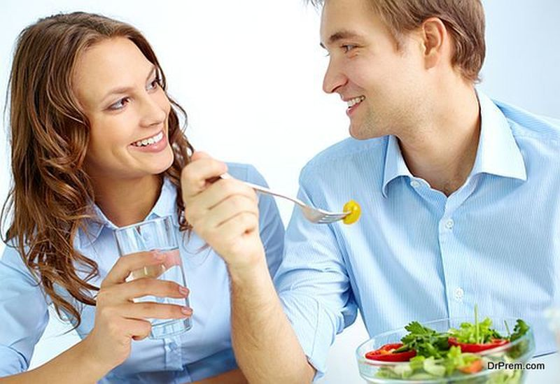 A couple sitting together and eating a boule of healthy food