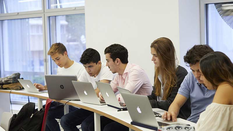 A group of people sitting at table and working in laptop